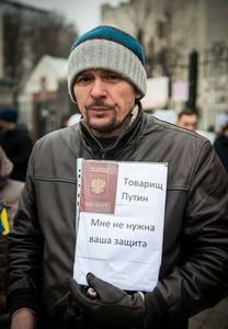 """Nápis v rukou muže: """"Soudruhu Putine, vaši ochranu nepotřebuji"""" s ruským pasem"""